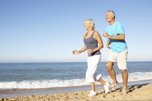 Older Couple Running Along Beach
